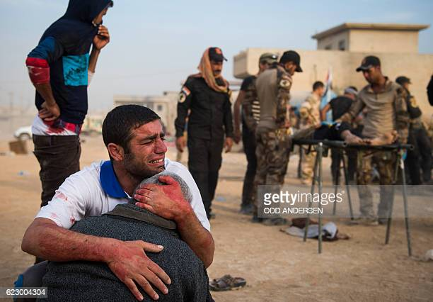 TOPSHOT Father and grandfather of 15yearold Shafiq mourn as Iraqi forces surround his body at an outdoor field clinic in the Samah neighbourhood in...