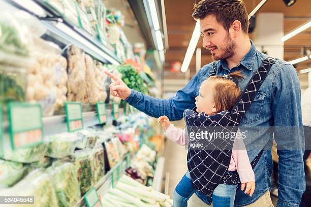 Father And His Baby Daughter Grocery Shopping.