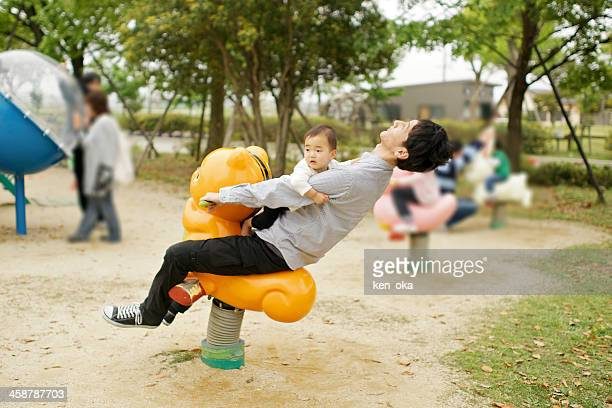 A father and his child play at playground