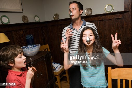 A father and his children hanging spoons on their noses