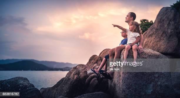 Padre y sus hijos mientras mira la puesta de sol sobre el mar