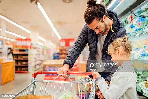 Father And His Daughter In A Supermarket.