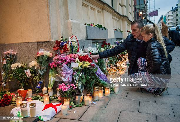 A father and his daughter place candles and flowers outside the French embassy in Stockholm on November 15 two days after the deadly attacks in...