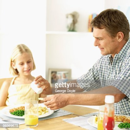 father and his daughter sitting at the dining table : Stock Photo