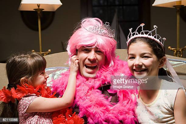 A father and his daughters playing fancy dress