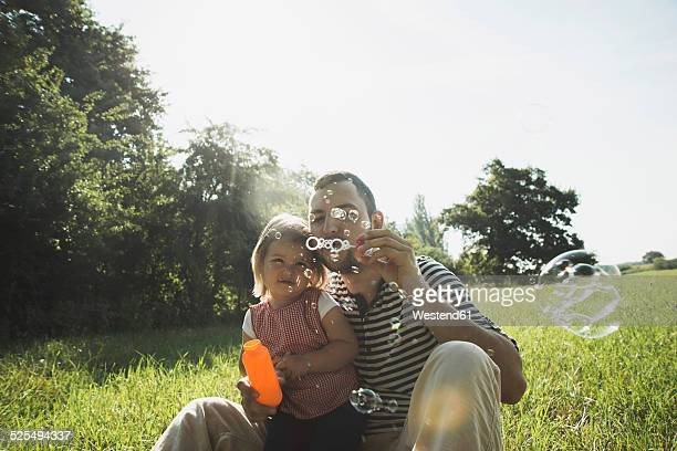 Father and his little daughter blowing soap bubbles