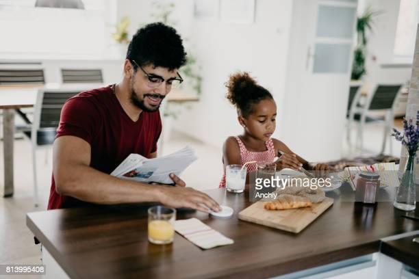 Vater und sein kleines Mädchen essen Frühstück auf dem Küchentisch