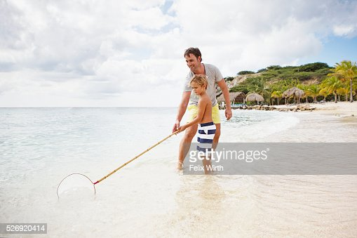Father and his son (4-5) fishing on beach : Stock-Foto