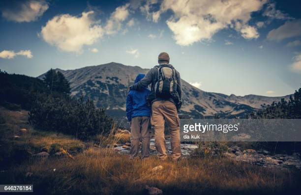 Father and his son hiking in mountains at sunset