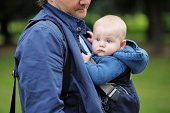 Father and his baby boy in a baby carrier outdoors