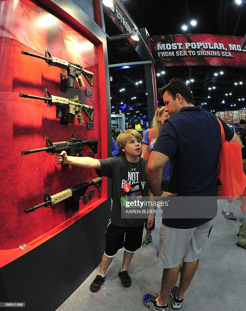 A father and his son look at Bushmaster semiautomatic rifles at the NRA Convention May 4 2013 in Houston Texas AFP PHOTO / Karen BLEIER