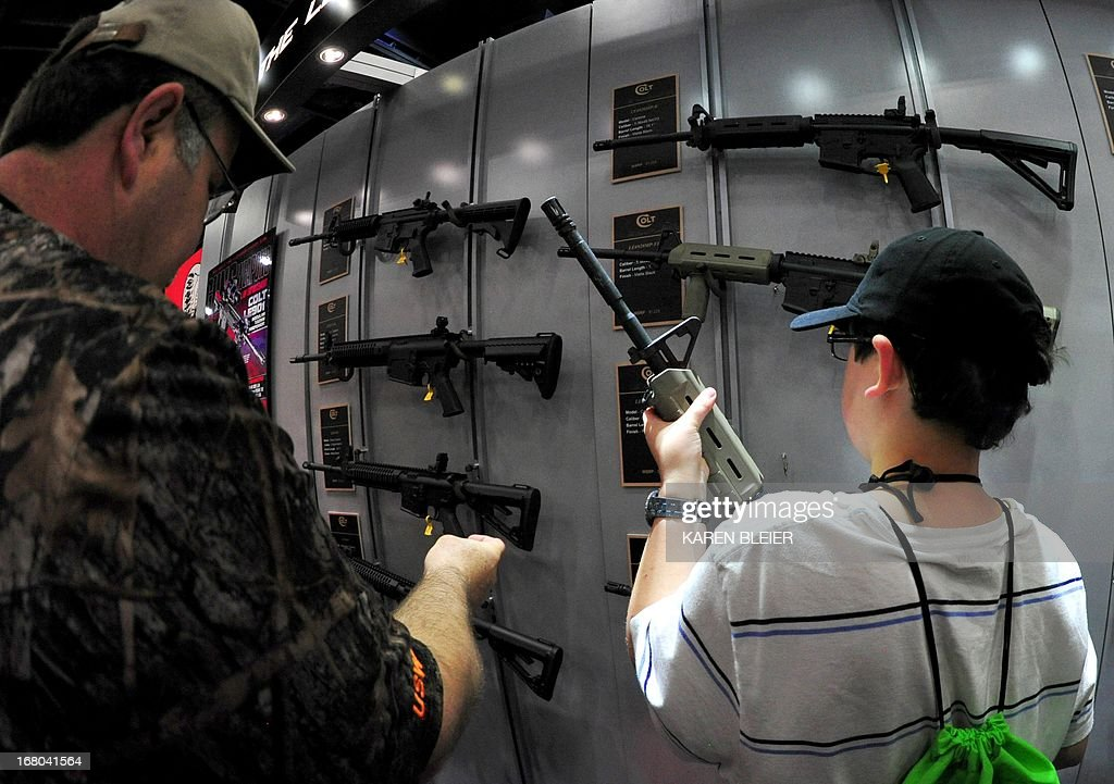 A father and his son look at Colt semiautomatic rifles at the NRA Convention on May 4 2013 in Houston Texas AFP PHOTO / Karen BLEIER