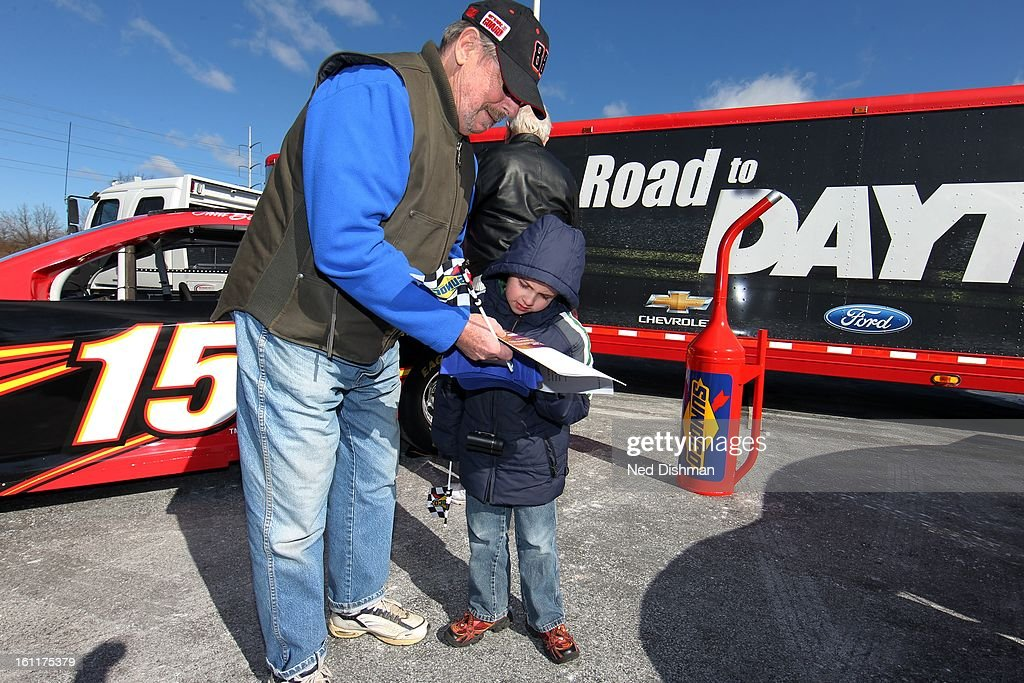 A father and his son look at free tickets to a Dover International Speedway race during a Road to Daytona Fueled By Sunoco Tour stop at the Sunoco Station on February 9, 2013 in Newark, Delaware.