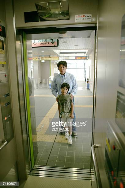 Father and his son standing in front of an escalator