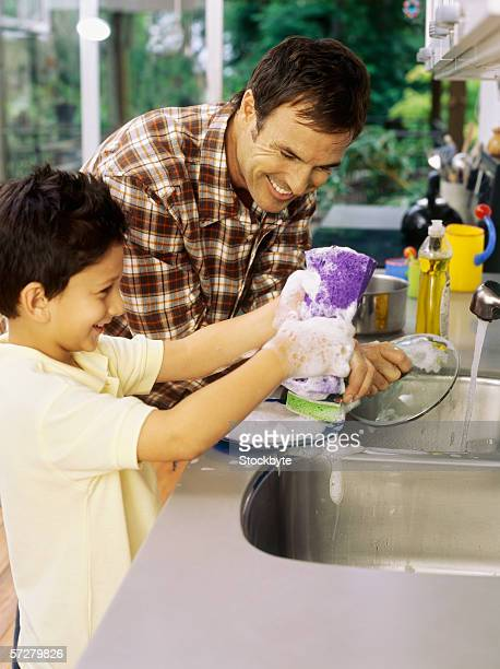 Father and his son washing dishes in the kitchen sink
