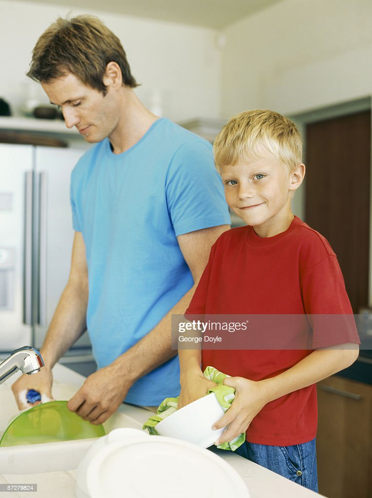 Father and his son washing dishes : Stock Photo
