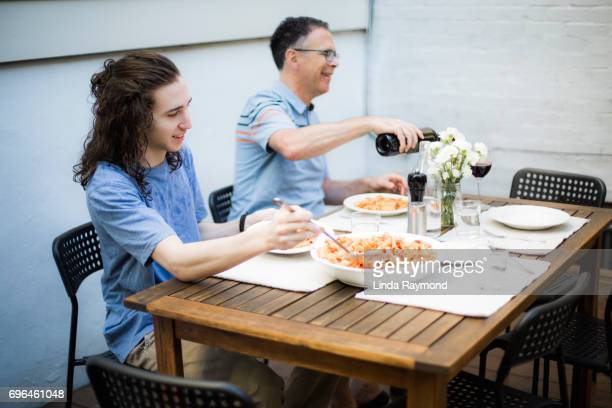A father and his teenage son sharing a meal  on an outdoor table