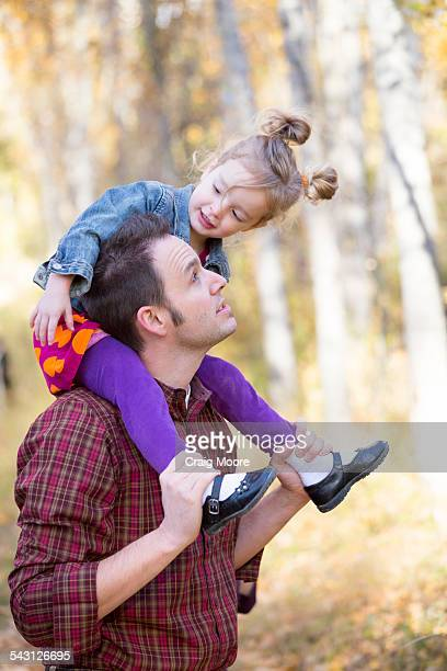 A father and his three year old daughter play during a fall time photo session in Kalispell, Montana.