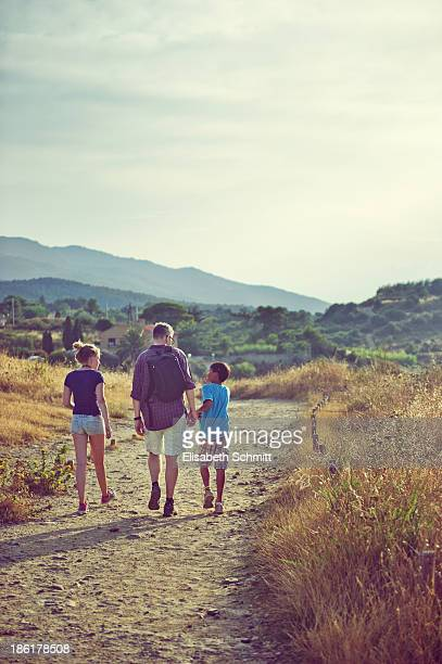 Father and his two children walking on pathway