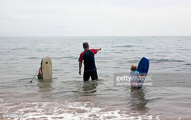 A father and his two children with boogy boards in the water at Miramar Beach on the Pacific Ocean Montecito is a wealthy beach community along...