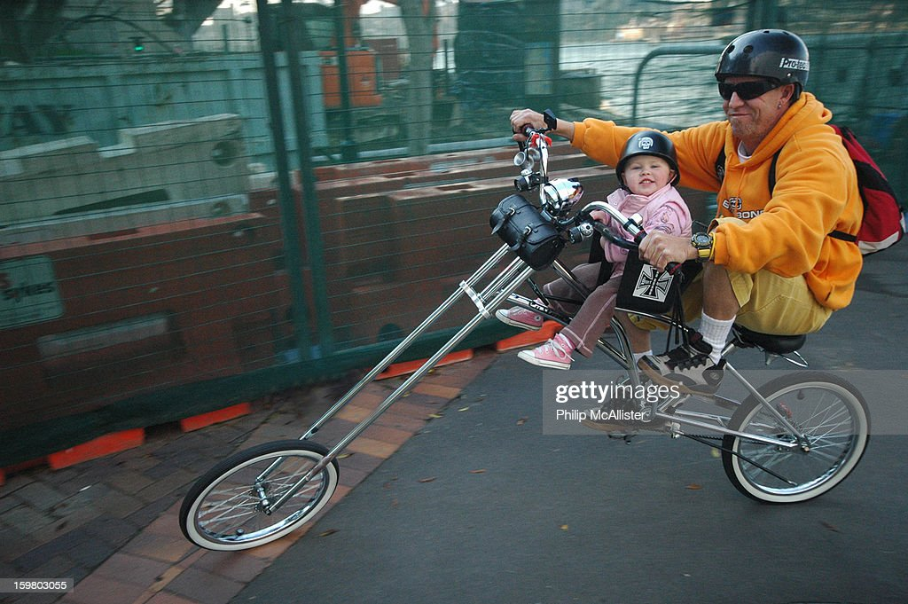 CONTENT] A father and his very young daughter are riding along on a motorcycle styled chopper bicycle.Both are smiling.The young child is seated on a child seat attached to the bike. The bicycle has elongated chopper style front forks.
