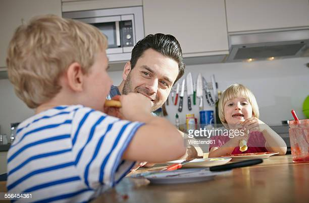 father and kids eating breakfast in kitchen