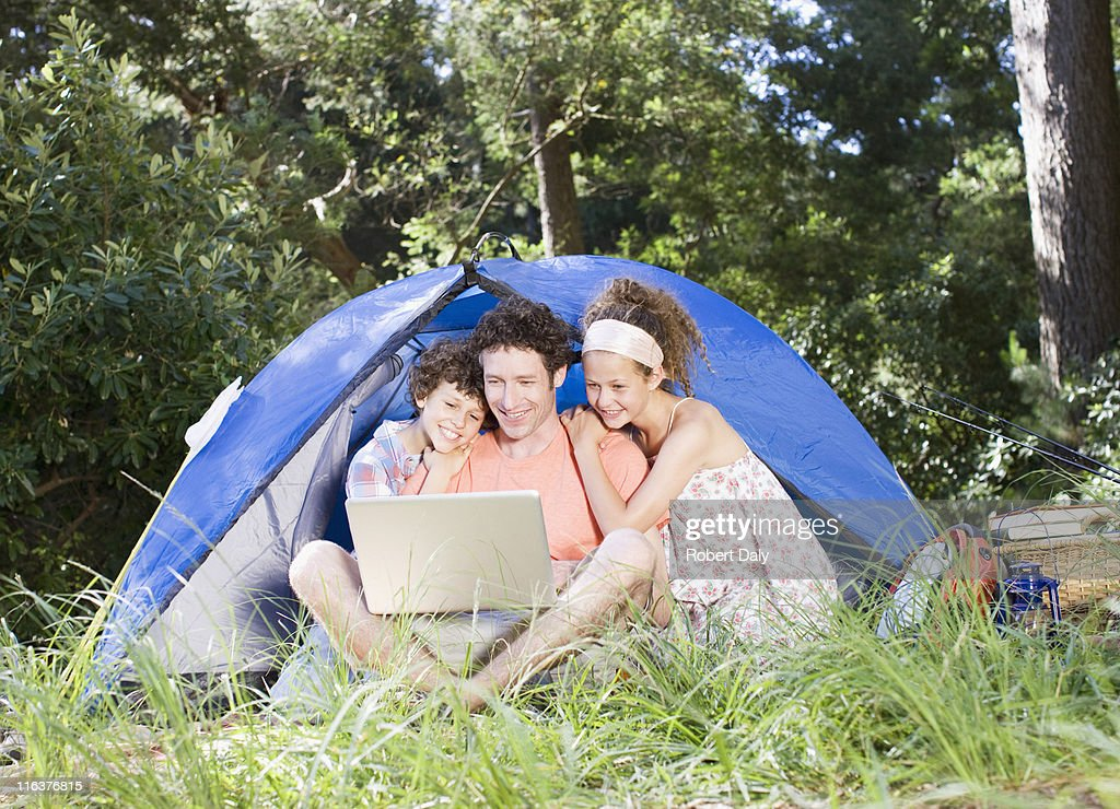 Father and kids using laptop outside tent : Stock Photo
