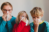 father and kids wiping and blowing nose, family infection or allergy