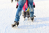 father and little daughter feet learning to skate in winter snow