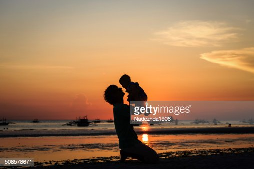father and little daughter on sunset beach : Stock Photo