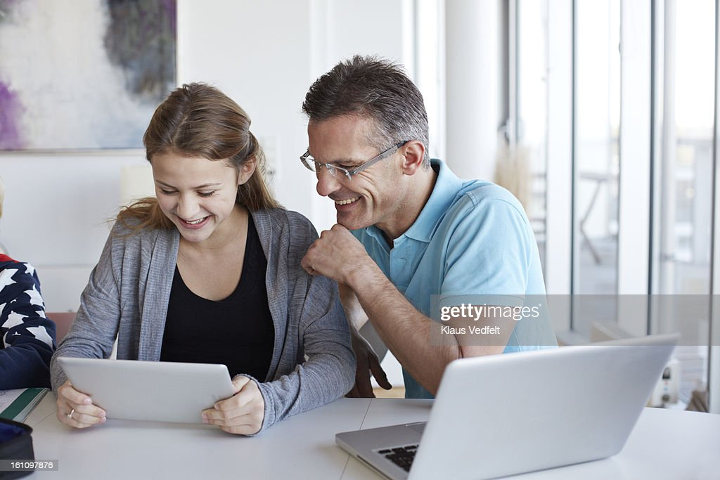 Father and looking at tablet toghether laughing : Stock Photo