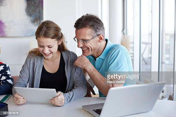 Father and looking at tablet toghether laughing