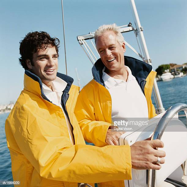 Father and Mature Son Stand Side by Side at the Helm of a Sailing Boat, Wearing Waterproof Jackets