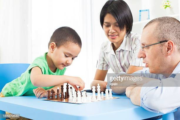 Father and mixed race son playing chess.