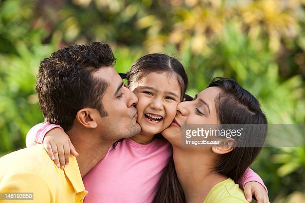 Father and mother kissing daughter (6-7) outdoors