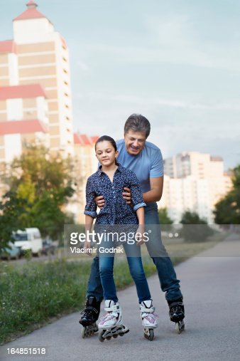 A father and mother rollerblading on a city sidewalk