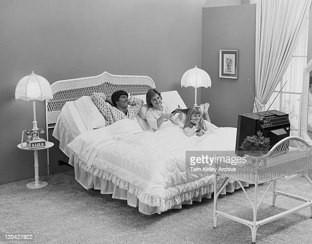 Father and mother with daughter lying on bed watching tv, smiling