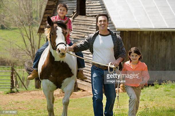Father and sister assisting boy horseback riding