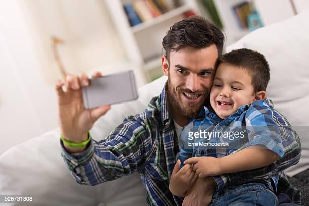 Vater und Sohn liegen posieren für ein selfie.