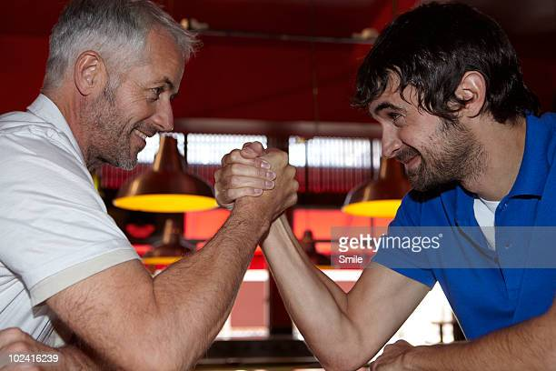Father and son arm wrestling in bar