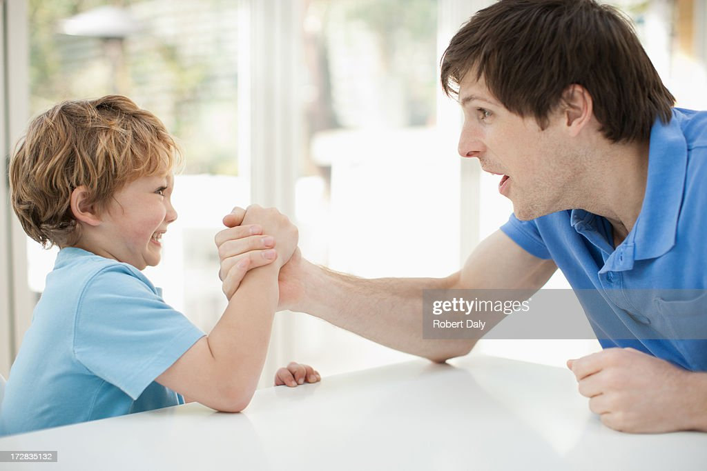 Father and son arm wrestling : Stock Photo