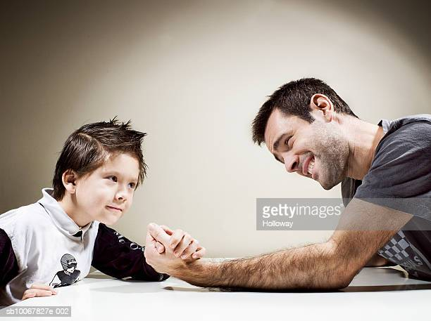 Father and son (4-5 years) arm wrestling, side view