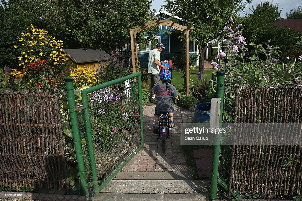 A father and son arrive at the garden and cottage they lease at the Oeynhausen Small Garden Association garden colony on August 29, 2013 in Berlin, Germany. At the Oeynhausen colony about 300 of its 438 gardens are currently threatened by real estate development, as are about another 24 colonies across the city. Berlin has about 900 garden colonies that are owned by the city and that provide urban dwellers who don't have land of their own the opportunity to maintain a garden and escape the stress of urban life. Berlin is currently undergoing a housing squeeze and city authorities are beginning to sell some of the colonies to developers, which has caused outrage in a city where the colonies of small gardens are a deep-seated tradition going back over a century.