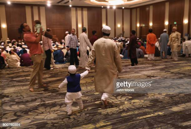 A father and son arrive for a prayer service celebrating the Islamic holiday of EidalFitr on June 25 2017 in Stamford Connecticut The holiday...