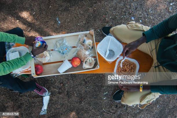 A father and son asylum seeker eat lunch provided by staff the Hub CARA centre feed nearly 1000 asylum seekers per day on July 27 2017 in Bologna...