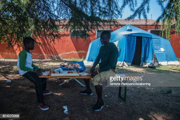 A father and son asylum seeker eat lunch provided by staff the Hub centre feed nearly 1000 asylum seekers per day on July 27 2017 in Bologna Italy In...
