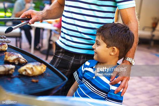 Father and son at barbecue grill in garden