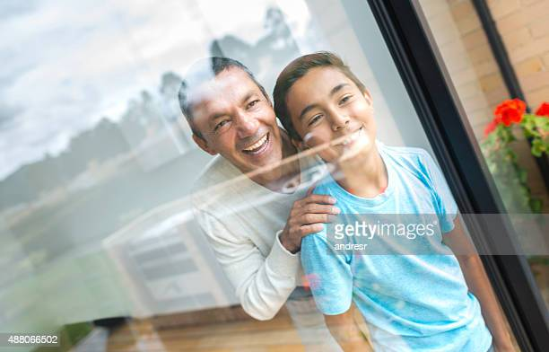 Father and son at home looking through window