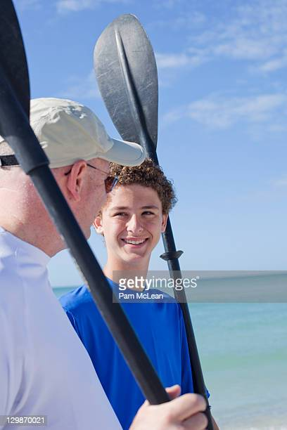 Father and son at the beach with kayak paddles