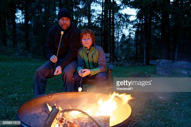 Father and son at the campfire roasting marshmallows